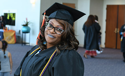 An Altierus Career College Houston Graduate Smiles in Her Cap and Gown